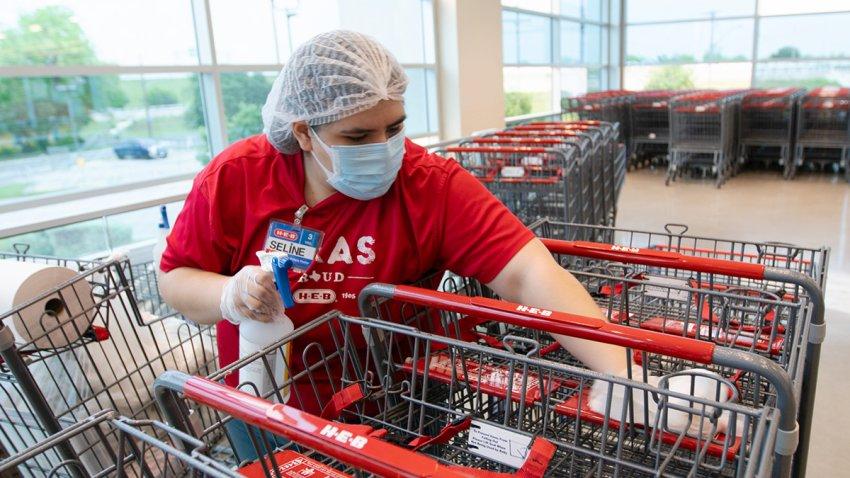 Empleada de HEB sanitizando carritos de compra