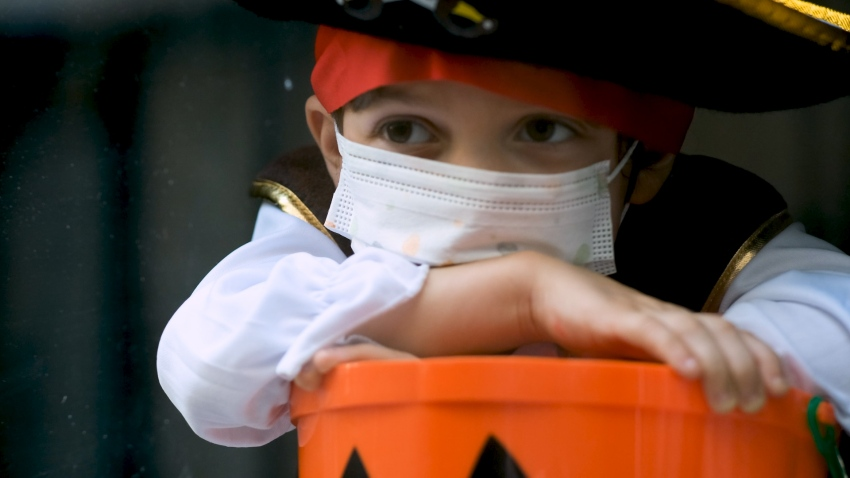 A child in pirate costume with a cloth mask
