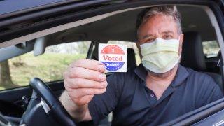 Hombre con mascarilla vota desde su auto