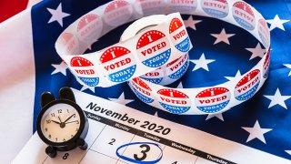 foto de un reloj, un calendario de noviembre y sellos que leen Yo vote en ingles.