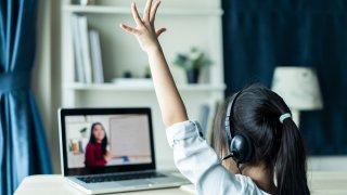 Niña levanta la mano durante una clase a distancia.