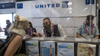 Personal de United atiende a pasajeros de un vuelo de San Francisco a Hawaii.