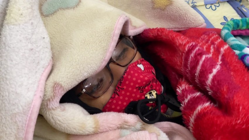 woman bundled to stay warm in cold inside her home