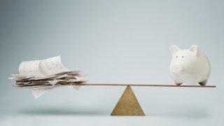 Foto muestra una balanza con un lado mostrando facturas y al otro una alcancía