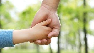 Niño de la mano con adulto